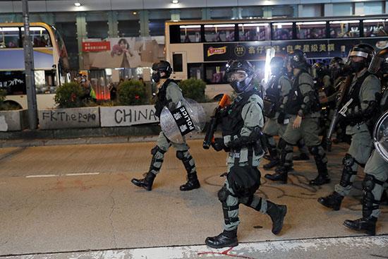 ضباط شرطة مكافحة الشغب يوجهون بنادقهم نحو المتظاهرين