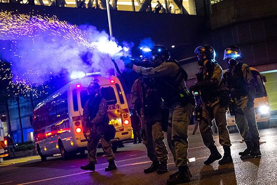 ضابط شرطة مكافحة الشغب يطلق حريق غاز مسيل للدموع باتجاه المتظاهرين