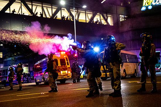 ضابط شرطة مكافحة الشغب يطلق حريق غاز مسيل للدموع
