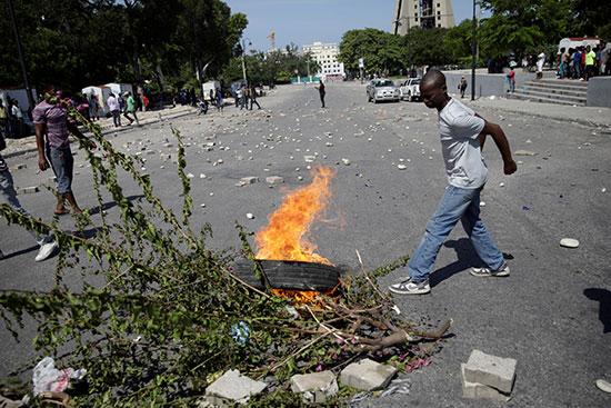 أحد المحتجين يضيء إطارًا على النار في شارع الشان دي مارس