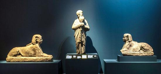 تمثال-لكاهن-يمسك-بأوزوريس-كانوب-بين-يديه-المحجبات-وتحيط-به-تمثالان-لأبو-الهول-تم-العثور-عليهما-معاً-في-ميناء-الإسكندرية