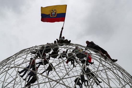 متظاهرون يرفعون علم الإكوادور