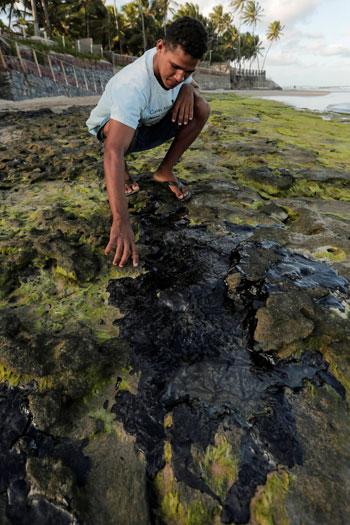 أحد المواطنين يتفقد البقع النفطية