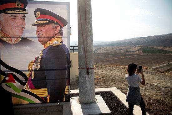 فتاة تلتقط صورا لمنطقة باقورة وبجوارها صورة العاهل الأردنى