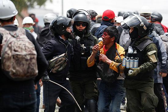 أفراد من قوات الأمن يعتقلون رجلاً مصاباً أثناء الاشتباكات بين مؤيدي إيفو موراليس وأنصار المعارضة في لاباز