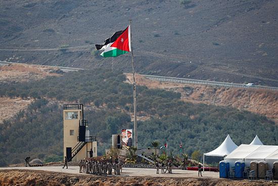 جنود أردنيون يتجمعون بالقرب من العلم الوطني الأردني  في منطقة باقورة