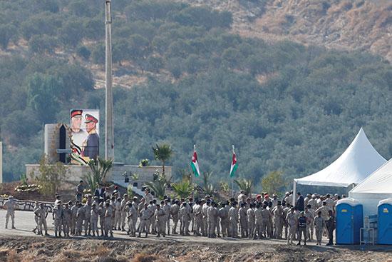 جنود أردنيون يتجمعون بالقرب من صورة للعاهل الأردني الملك عبد الله ووالده الراحل الملك حسين في المنطقة الحدودية بين إسرائيل والأردن