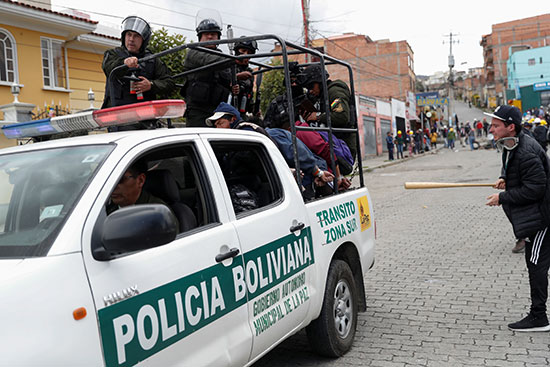 ضباط الشرطة يحملون متظاهرين احتُجزوا خلال اشتباكات بين أنصار الرئيس البوليفي إيفو موراليس وأنصار المعارضة في لاباز