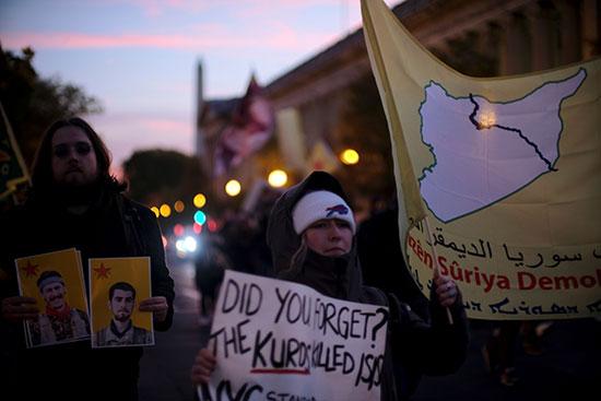 المحتجون يرفعون علم لقوات سوريا الديمقراطية