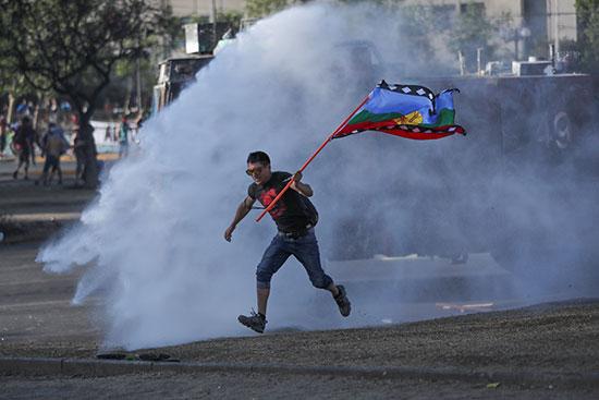 متظاهر يركد ويرفع علم التشيلى بينما تنفجر اسطوانة غاز مسيلة للدموع