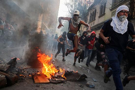 المتظاهرون يقفزون من فوق اطارات مشتعلة بالشوراع