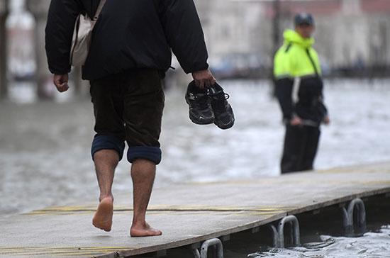 رجل يحمل حذاءه للسير فى مياه الفيضانات