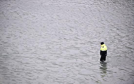 أحد العمال وسط مياه الفيضانات