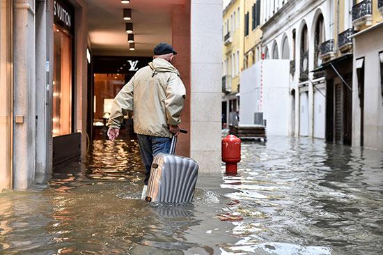 مواطن يسير فى المياه ساحبا حقيبته