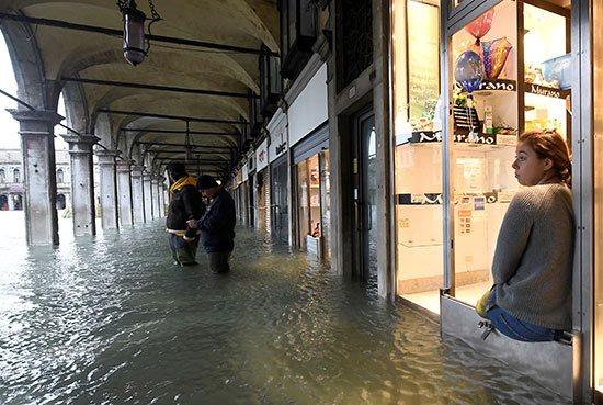 فتاة تتجلس أمام متجرها وتنظر إلى مياه الفيضان
