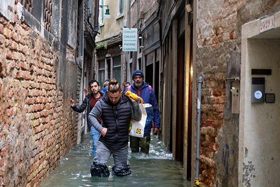الناس يرتدون الأكياس البلاستيكية لوقايتهم من المياه