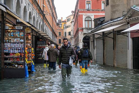 الناس يسيرون والمياه تغرق الشوارع