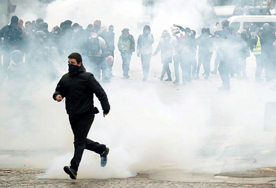 متظاهر يركض بعيدا عن دخان الغاز