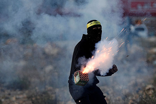 متظاهر فلسطيني يطلق ألعاب نارية أثناء مظاهرة مناهضة لإسرائيل بالقرب من مستوطنة بيت إيل