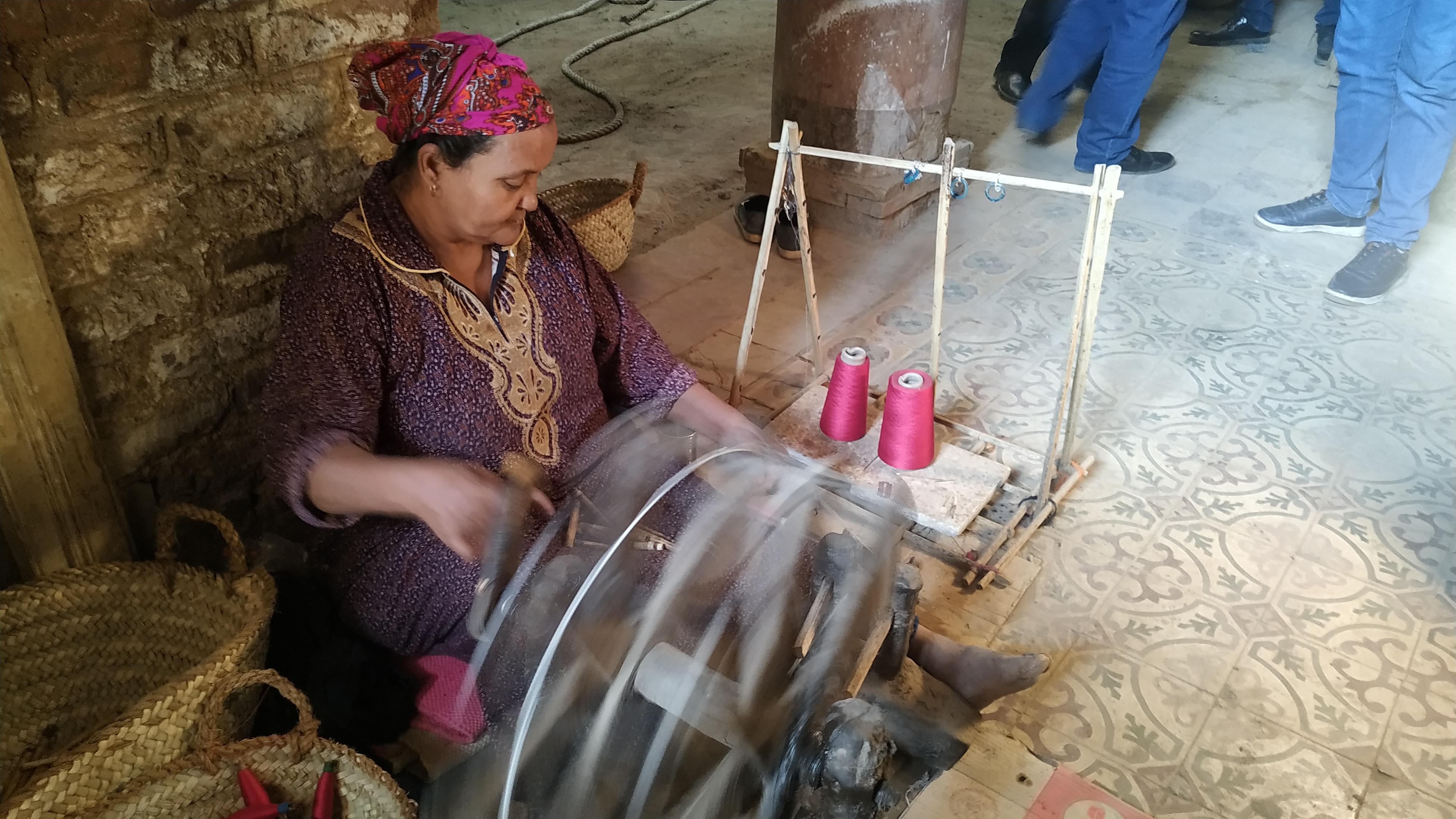 إحدى السيدات تجمع الخيوط على البكرات
