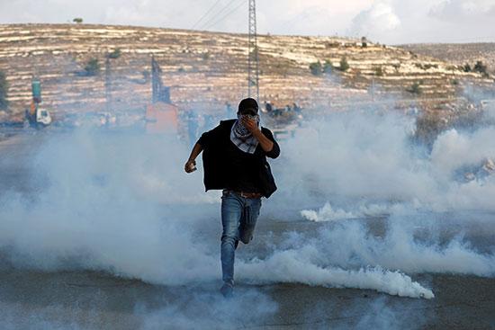 متظاهر فلسطيني يهرب من الغاز المسيل للدموع الذي أطلقته القوات الإسرائيلية