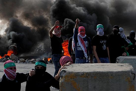 متظاهرون فلسطينيون ملثمون يبدون إشارة خلال مظاهرة مناهضة لإسرائيل