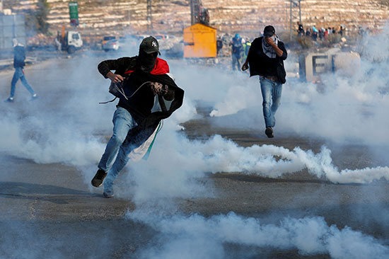 متظاهرون فلسطينيون يفرون من الغاز المسيل للدموع الذي أطلقته القوات الإسرائيلية