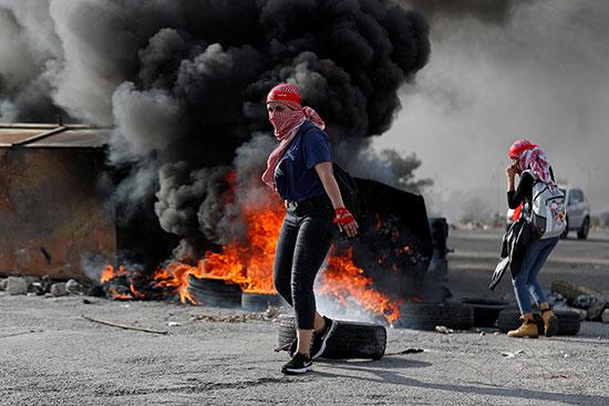 متظاهرة فلسطينية أمام إطارات محترقة أثناء مظاهرة مناهضة لإسرائيل