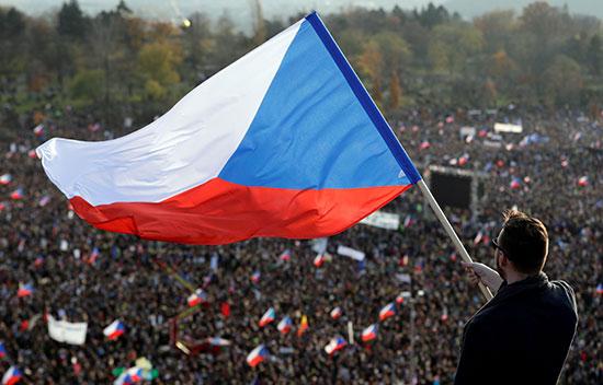 محتج يرفع علم التشيك خلال احتجاجات ضد الحكومة