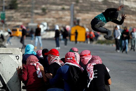 المتظاهرون الفلسطينيون يتسترون بينما يقفز زملائهم خلال مظاهرة مناهضة لإسرائيل