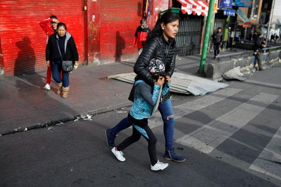 متظاهرة تحمى طفلها من الغاز المسيل