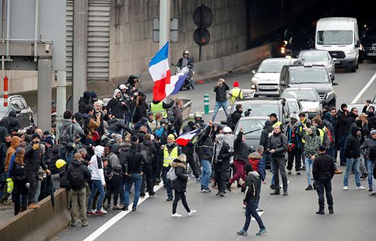 أصحاب السترات يرفعون العلم الفرنسى خلال المظاهرات