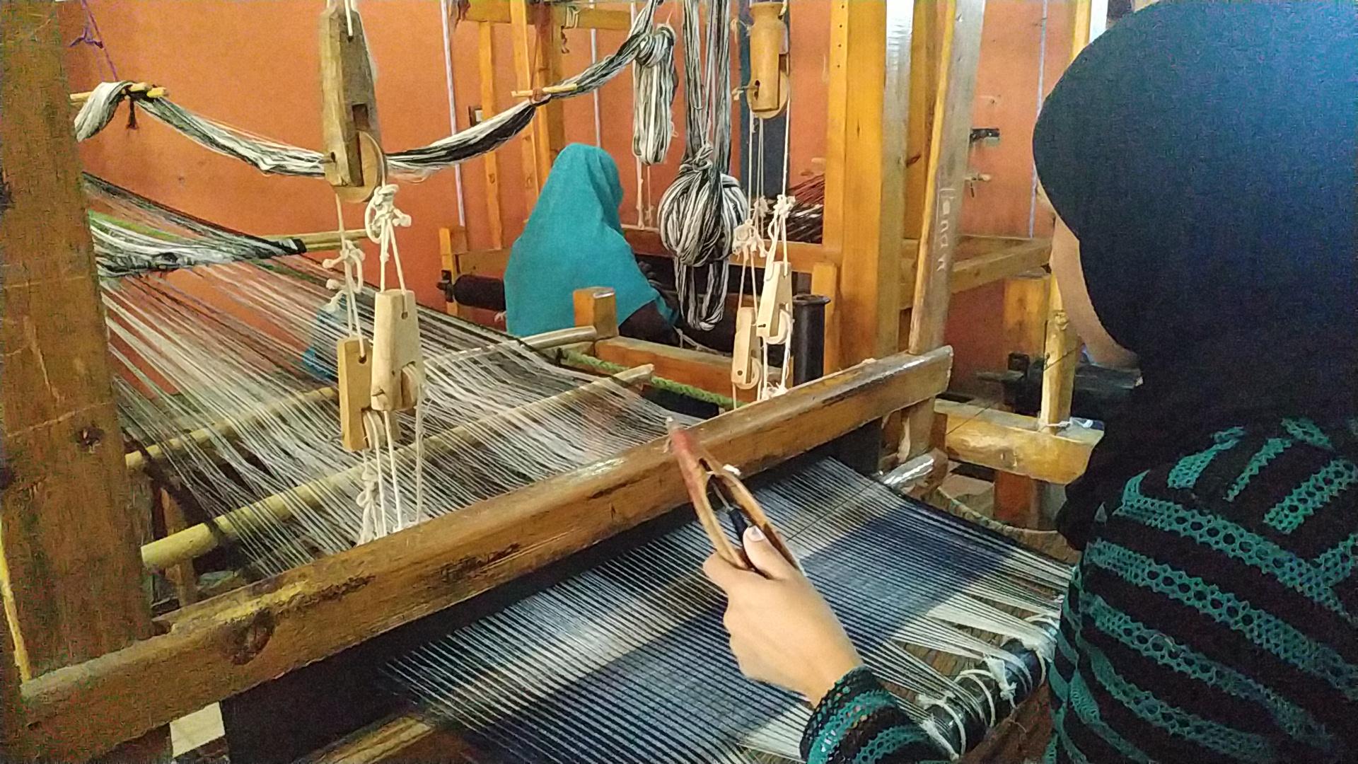 فتاة تصنع شال على نول الفركة