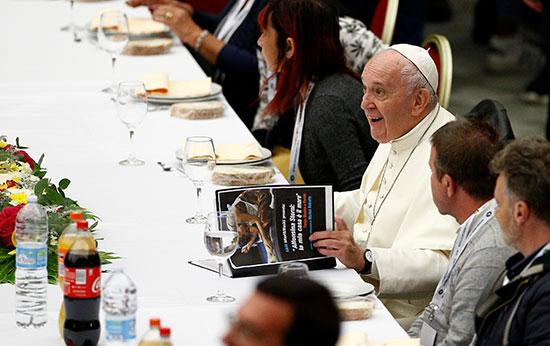 بابا الفاتيكان يجلس وسط الحضور ويطالع إحدى المجلات