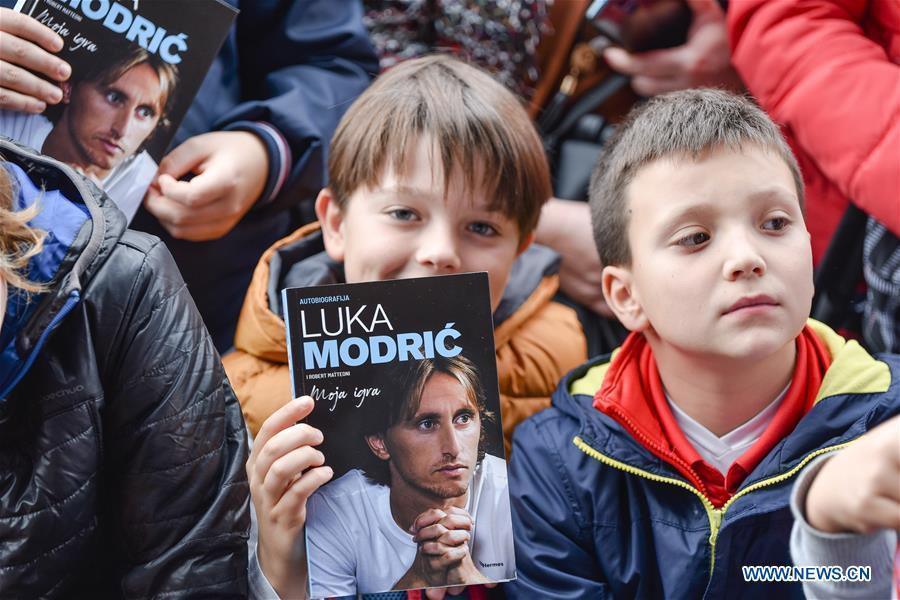 الاطفال يحملون كتاب لوكا