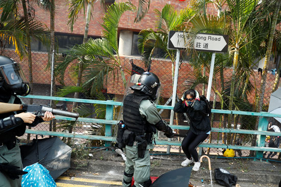 متظاهرة-تقف-أمام-أحد-قوات-الشرطة-فى-هونج-كونج