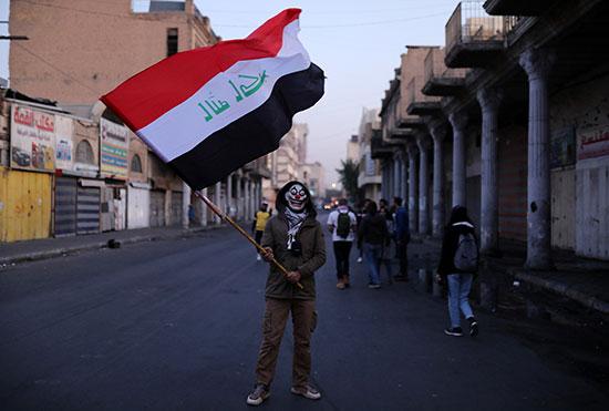 متظاهر يرفع العلم العراقى