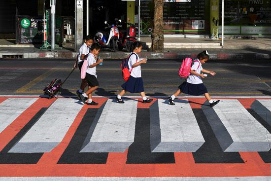 أطفال يسيرون على ممر المشاة