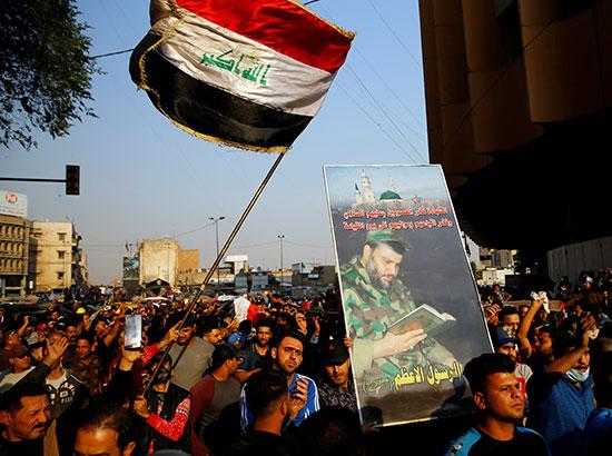 المتظاهرون يرفعون الأعلام العراقية