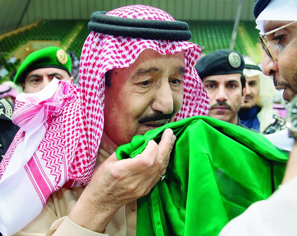 الملك سلمان بن عبدالعزيز يقبل علم بلاده
