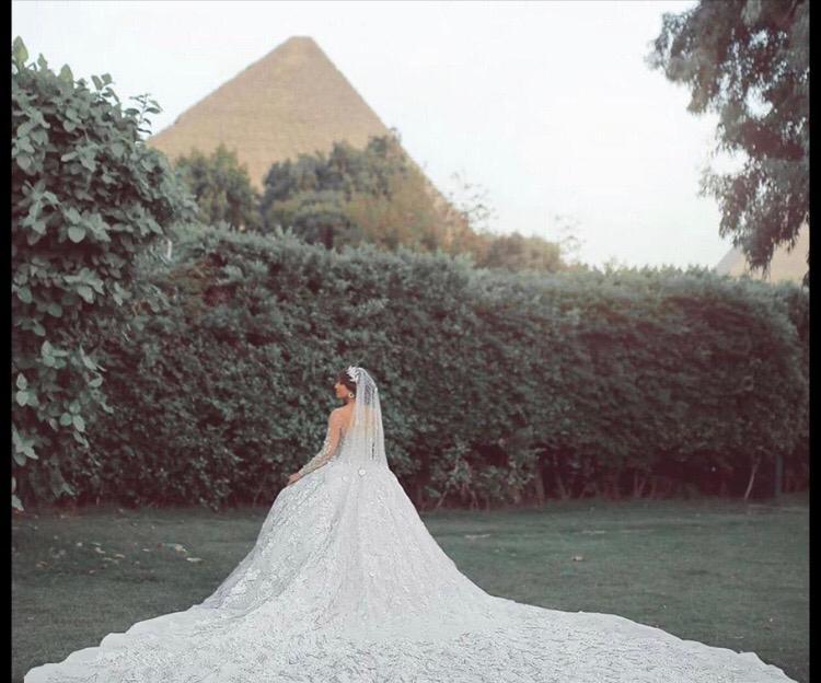 عروس تستعرض فستانها أمام الأهرامات