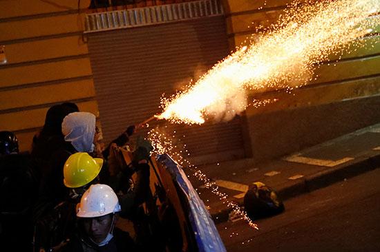 متظاهرون يلقون الألعاب النارية على قوات الأمن