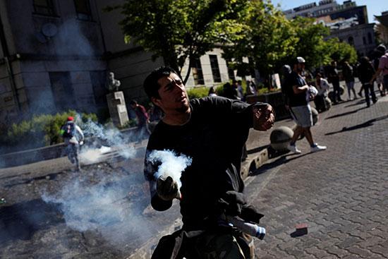 متظاهر يلقى قنبلة غاز على الشرطة
