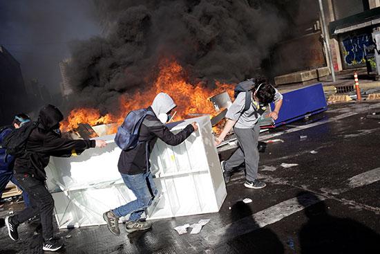 متظاهرون يضعون المتاريس أمام قوات الشرطة