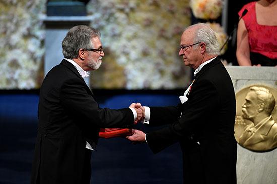 الأستاذ الأمريكى جريج ل. سيمينزا يصافح الملك السويدى كارل غوستاف