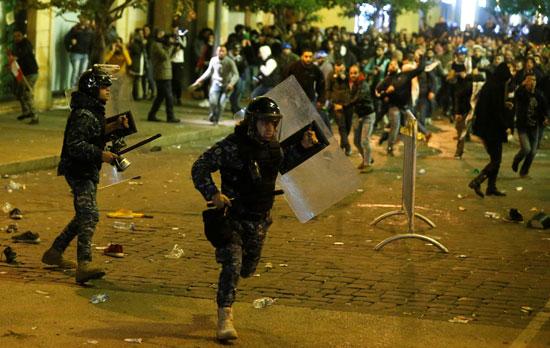 أحد عناصر الشرطة يفر من حجارة المحتجين