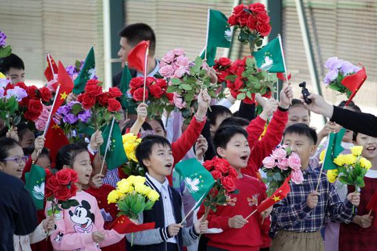 أطفال-بالإقليم-يرفعون-أعلام-الصين-وماكاو
