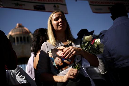 سيدة تحمل الورود على ارواح الضحايا