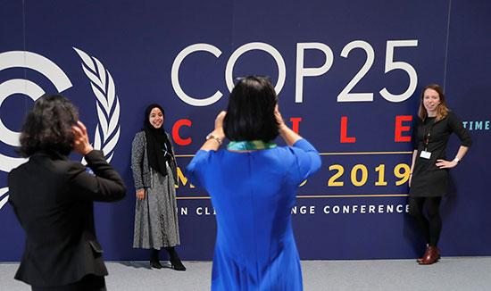 أشخاص يلتقطون صورة تحمل شعار مؤتمر الأمم المتحدة المعني بتغير المناخ