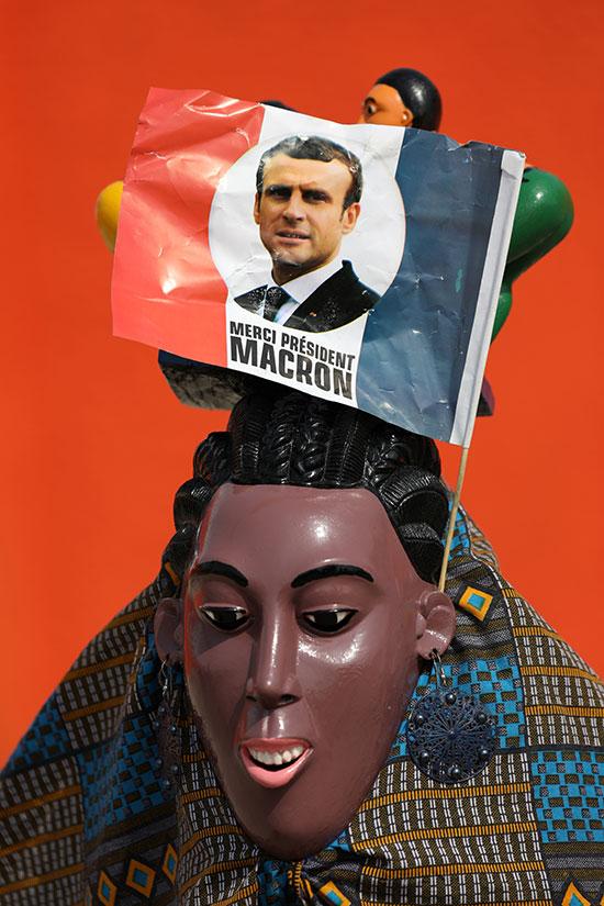 علم صغير يصور الرئيس الفرنسي إيمانويل ماكرون مرفق بقناع قبل وصوله ساحل العاج